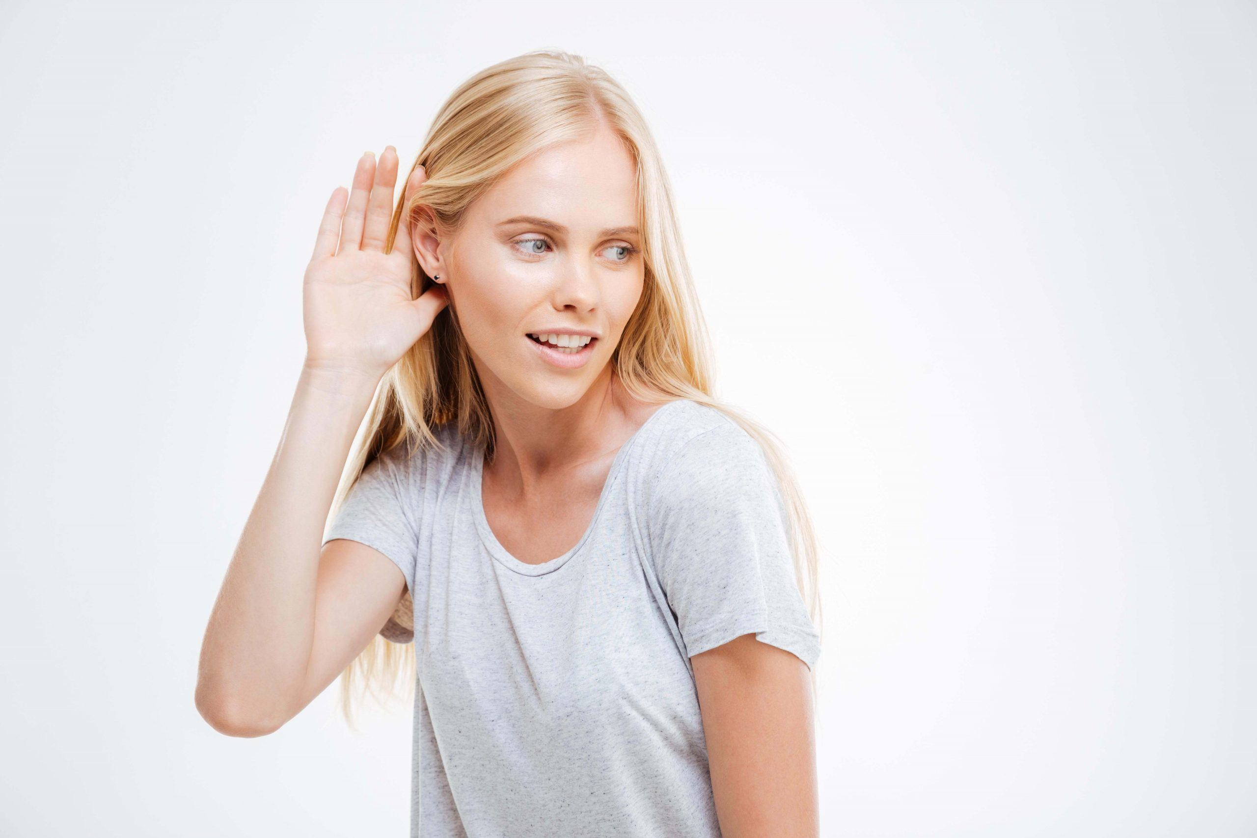 beautiful-blonde-woman-with-hand-at-the-ear-to-hear-better-isolated-on-a-white-background